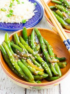 wooden bowl filled with green beans cooked in asian sauce