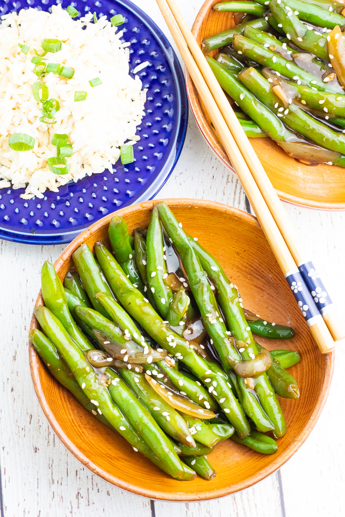 overhead shot of wooden bowl filled with asian green beans and chopsticks