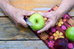 elderly person peeling apple