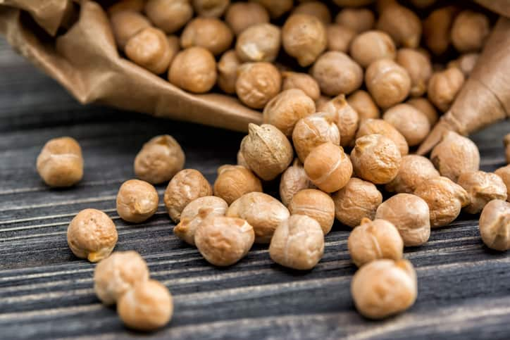 Raw chickpeas in paper bag on wooden background. Healthy food