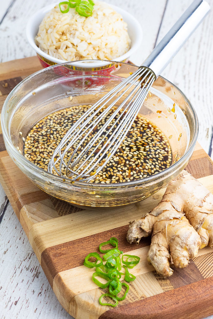 sweet ginger sauce with sesame seeds in clear bowl with whisk
