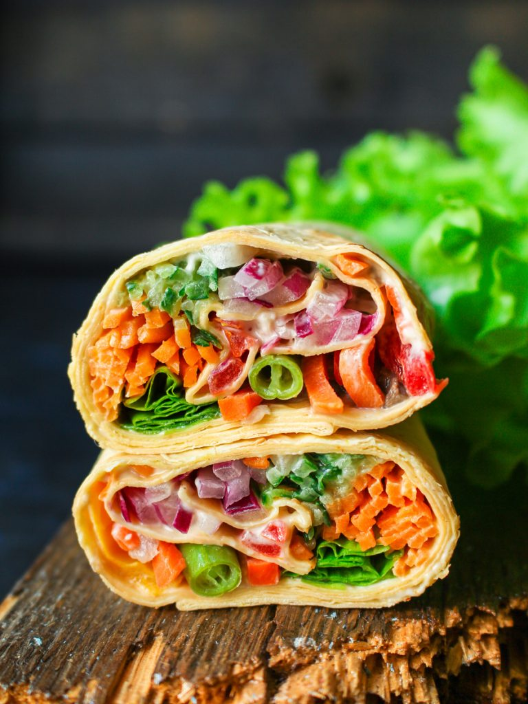 2 veggie wraps stacked on top of each other on a wooden board with lettuce in background