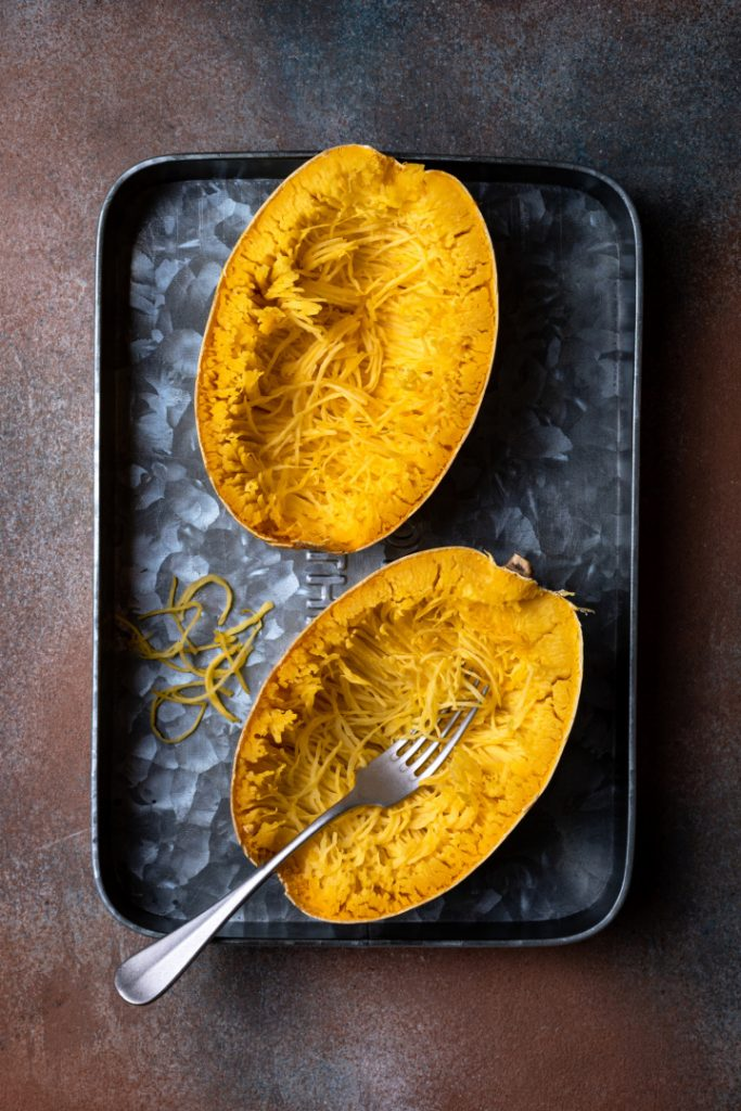 spaghetti squash baked and sliced in half on baking sheet with spoon