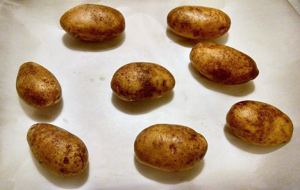 whole potatoes on baking sheet