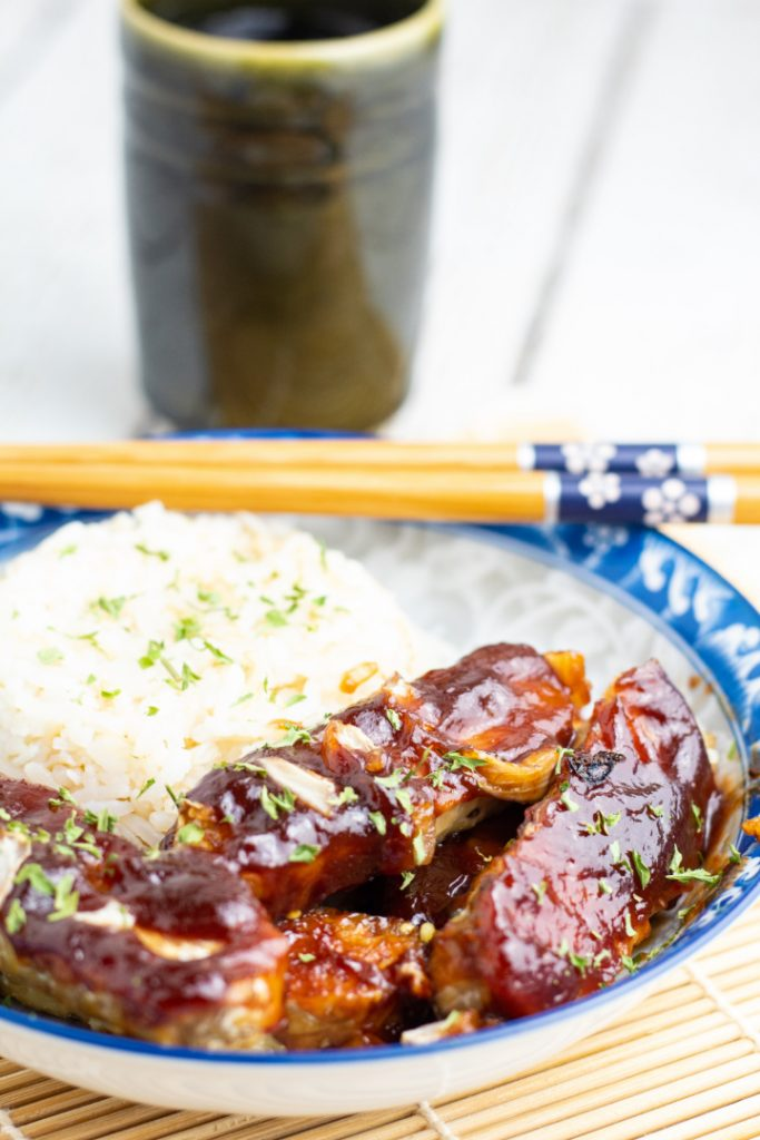 bbq tempeh in asian blue bowl with rice and chopsticks