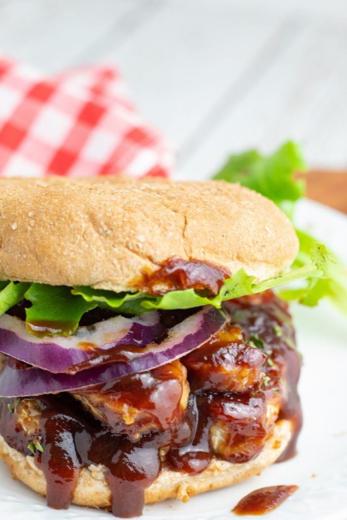 bbq tempeh on whole wheat bun with onion and lettuce
