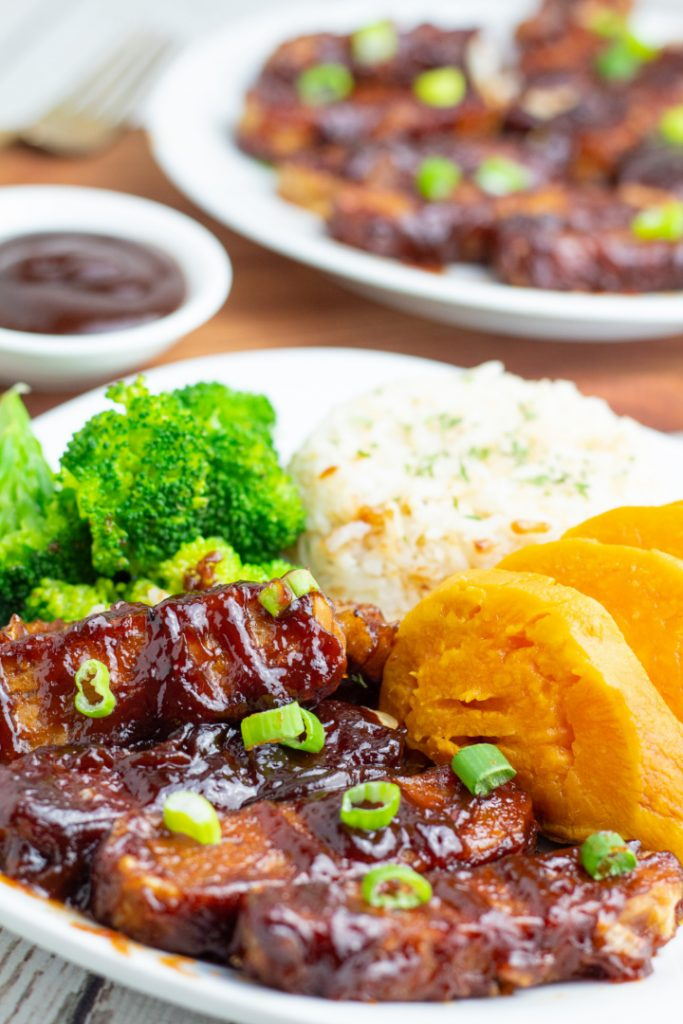plate with bbq tempeh ribs, baked sweet potato, rice, and broccoli