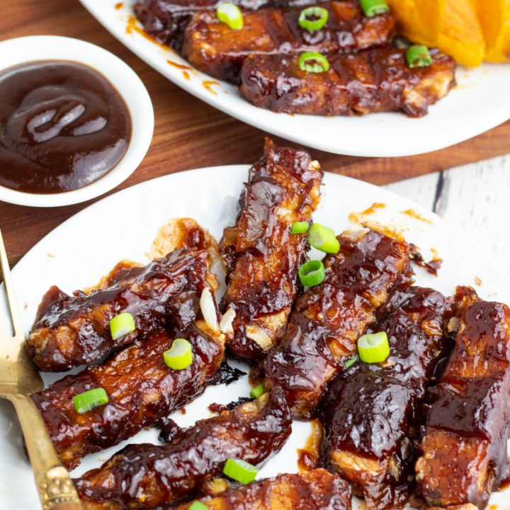 white plate with bbq tempeh strips and antique fork