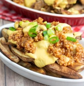 two plates of vegan chili cheese fries