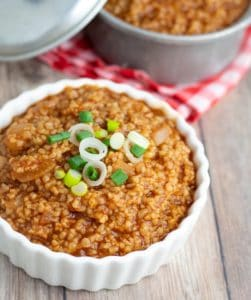bulgur chili in white bowl topped with chives