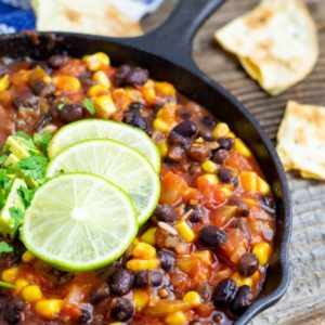 vegan salsa chili in cast iron pan with lime on wood table