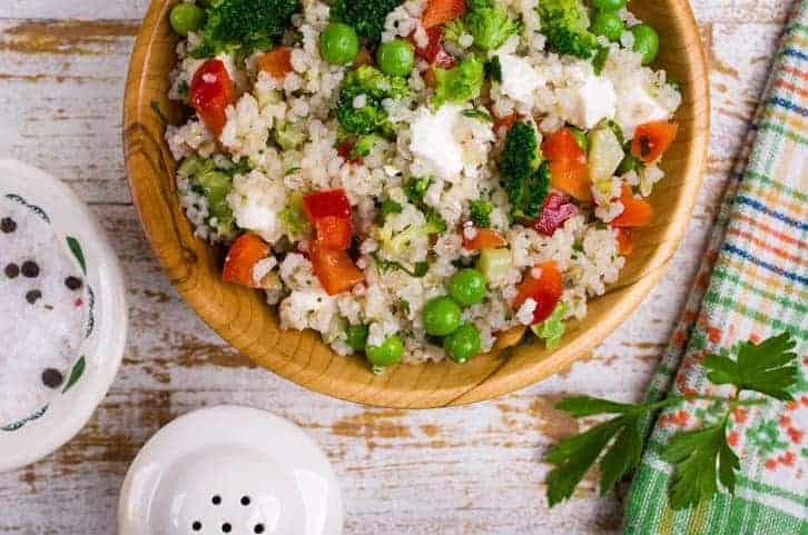 bulgur wheat salad in wooden bowl with broccoli peas carrots