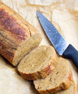 seitan roast on parchment paper with knife