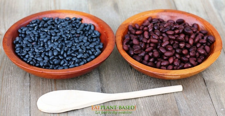 Uncooked black beans on the left and cooked black beans on the right of wooden table