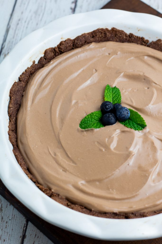 close up of chocolate vegan pie in white pie plate topped with mint leaves and blueberries
