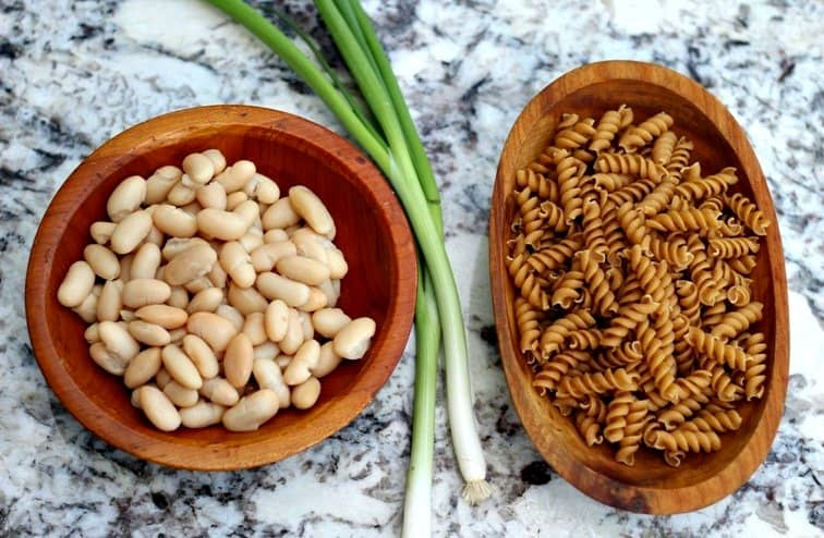 beans and pasta in wooden bowls on counter top