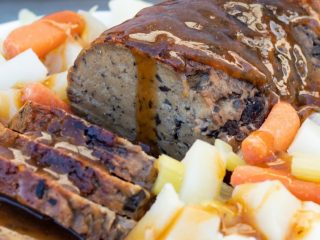 vegan seitan mushroom roast on platter with potatoes and carrots
