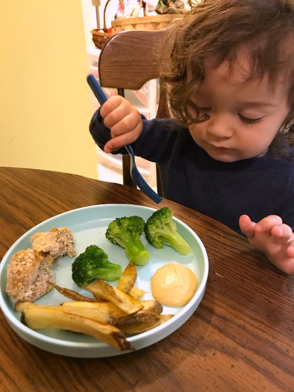 baby eating broccoli and baked French fries with vegan cheese sauce