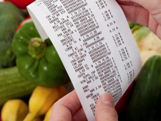hands holding grocery receipt with vegetable in background