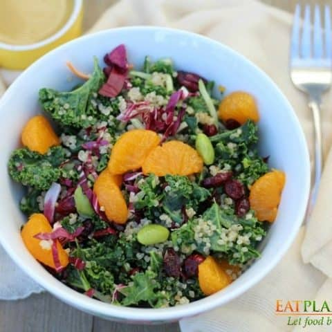 quinoa kale salad in white bowl with fork
