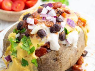 vegan potato taco on white plate with beans, vegan cheese, and sour cream