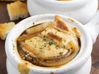close up of vegan french onion soup in white crock bowl