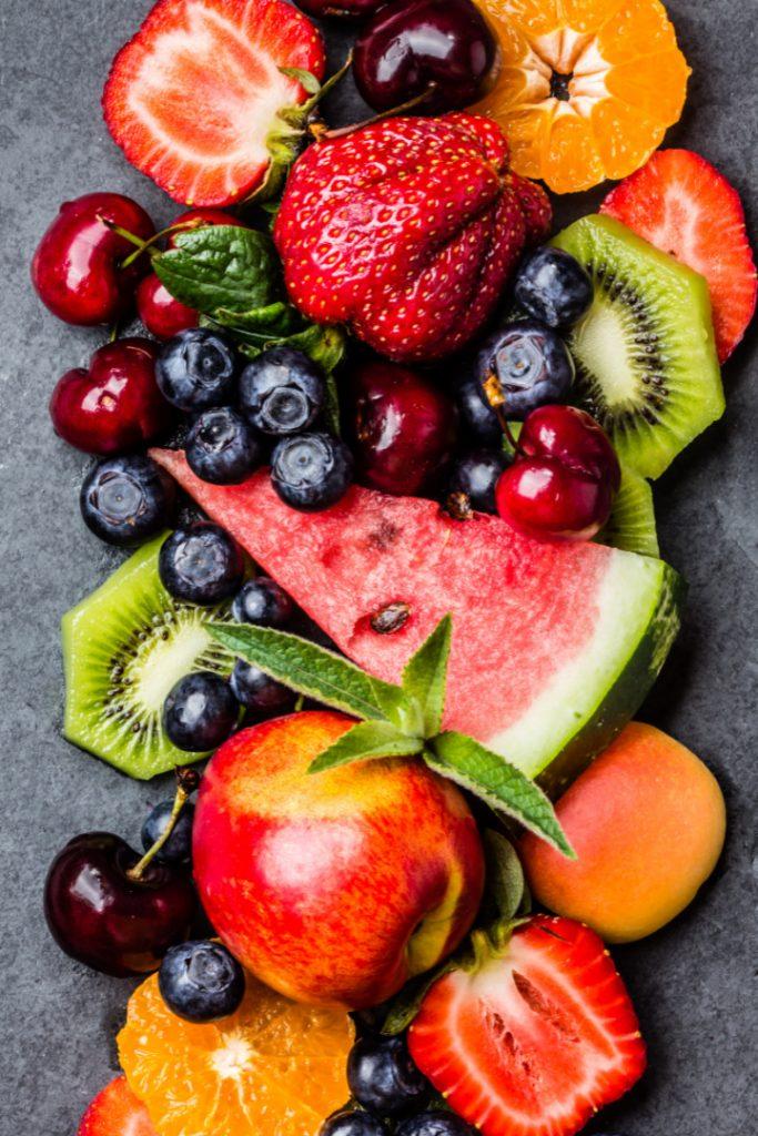 Assortment of summer fresh berries and fruits. Mix of blueberry, cherry, kiwi watermelon, strowberry, tangarine, mandarine peach, clementine on black slate plate on black slate plate. Top view