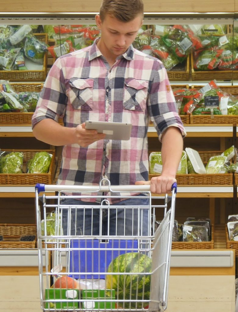 man shopping in grocery store produce section pushing buggy and reading grocery list