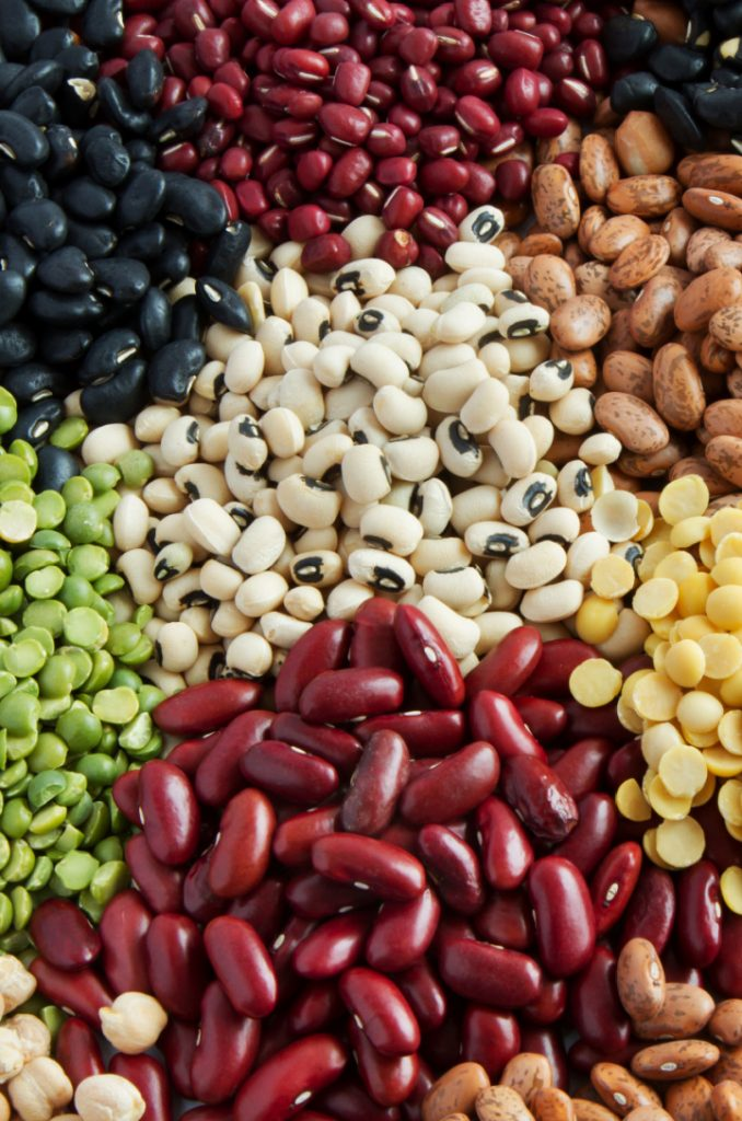 different types and colors of legumes spread out on table