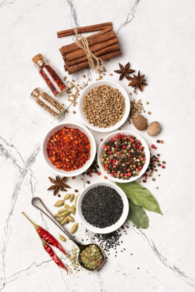spice bowls and spoons with variety of different spices on white background