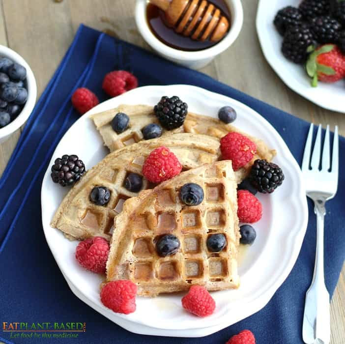 vegan waffles topped with berries and maple syrup