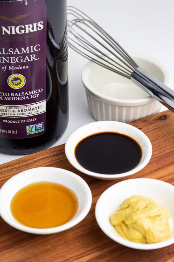 balsamic vinegar, dijion mustard, and maple syrup in white bowls with whisk