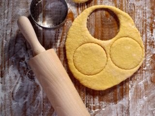 rolling pin, cookie cutter, and dough on wooden board