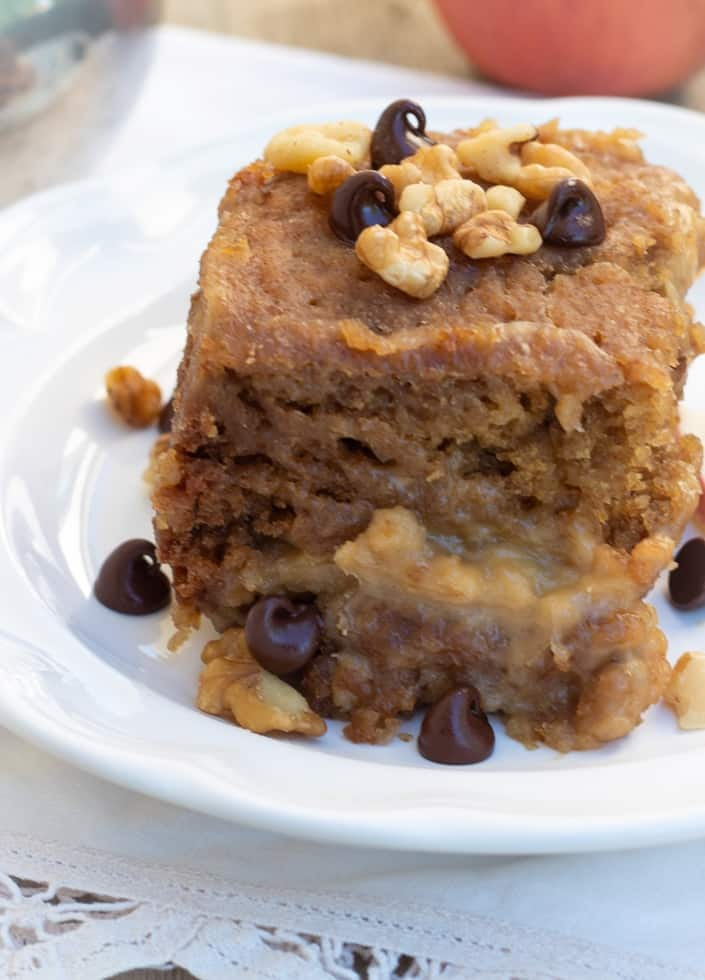 vanilla crockpot cake slice on white plate topped with walnuts