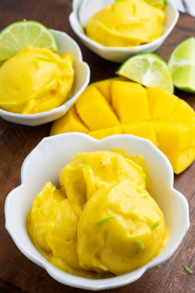 mango ice cream in white scalloped bowl with slice mango in background