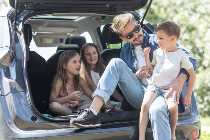 father and kids sharing healthy snacks on road trip