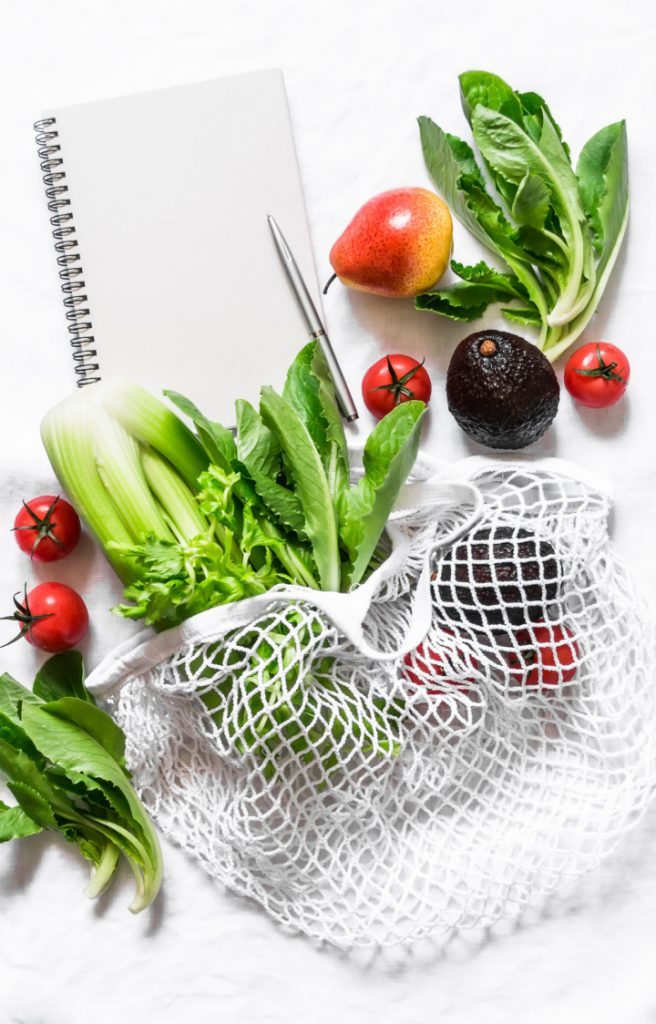 mesh grocery bag with veggies on white background