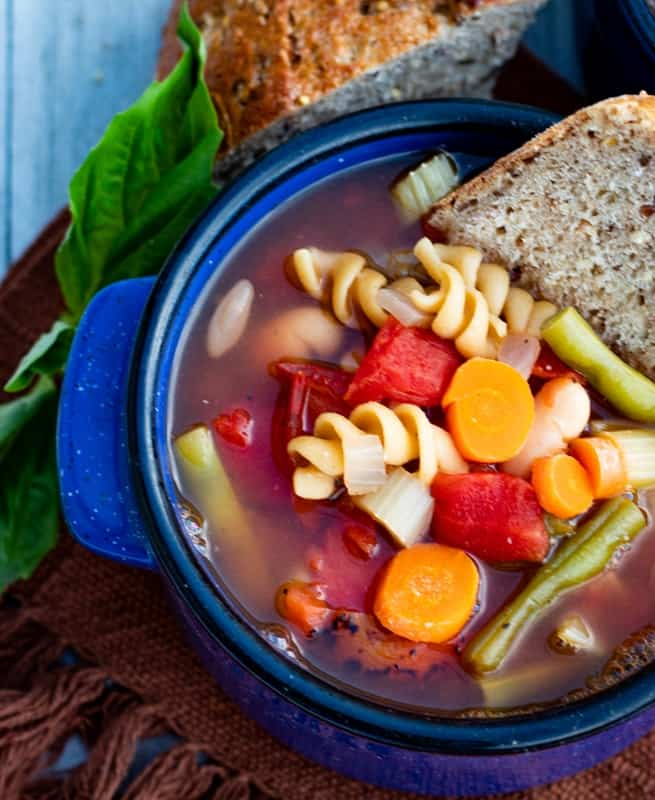 vegan minestrone soup in bright blue bowl with bread