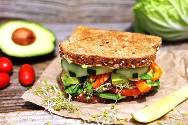 vegan hummus sandwich on brown paper with avocado in backgroud