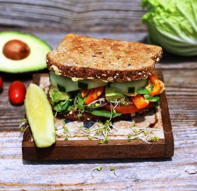 Veggie Sandwich with hummus on wooden board
