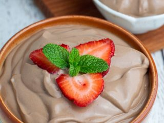 vegan chocolate mousse topped with strawberries and mint leaves
