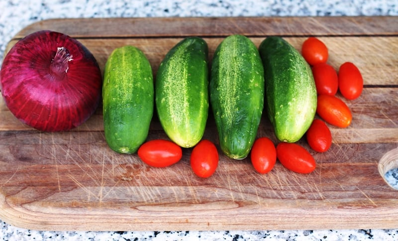 cucumbers, tomatoes, and purple onoin on cutting board