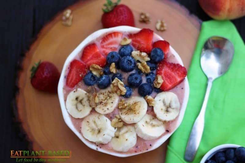 smoothie bowl topped with strawberries, bananas, and blueberries
