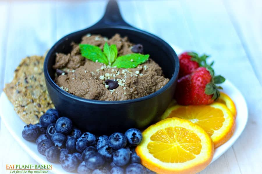 chocolate hummus in black bowl on tray with fruit and crackers