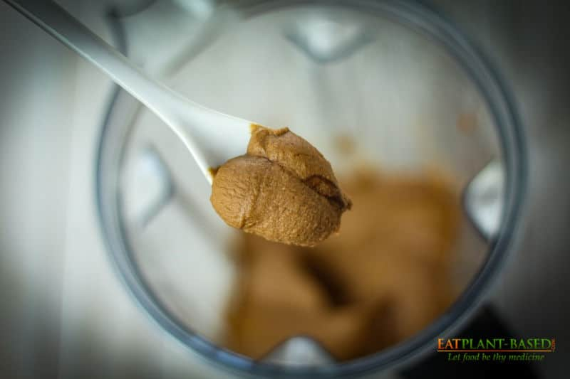 close up of a spoonful of dessert hummus over blender