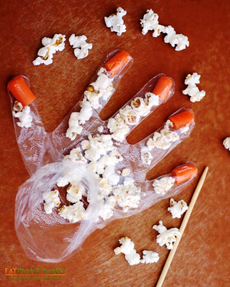 popcorn being added to halloween popcorn hands