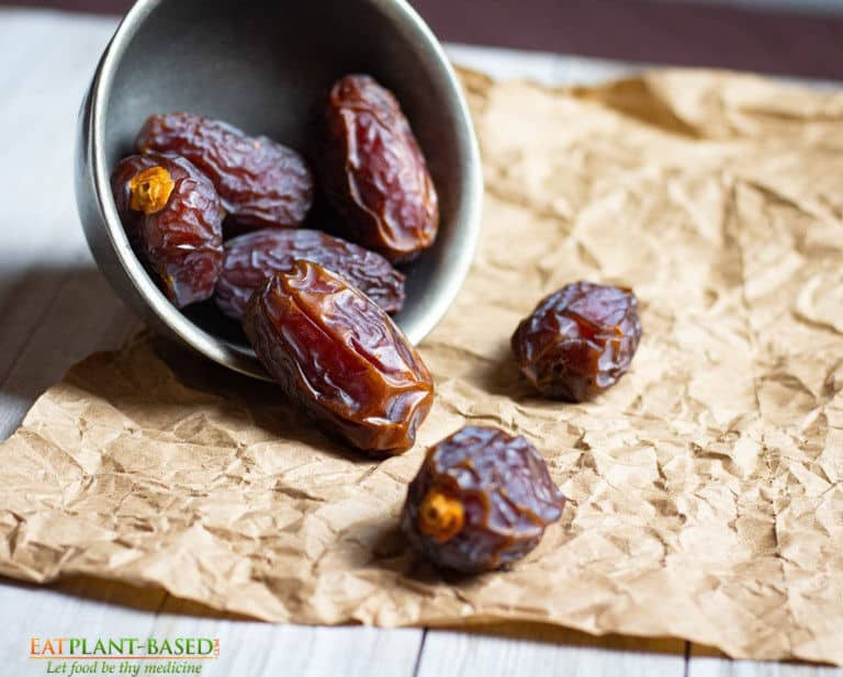 dates falling out of a bowl onto brown paper on a table