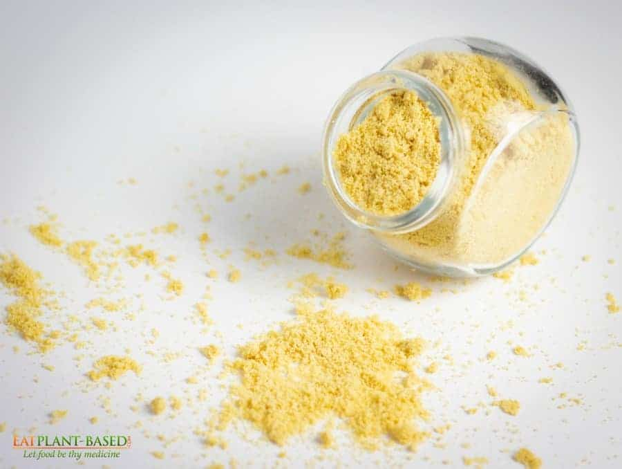 vegan parmesan in glass jar with some sprinkled over white table