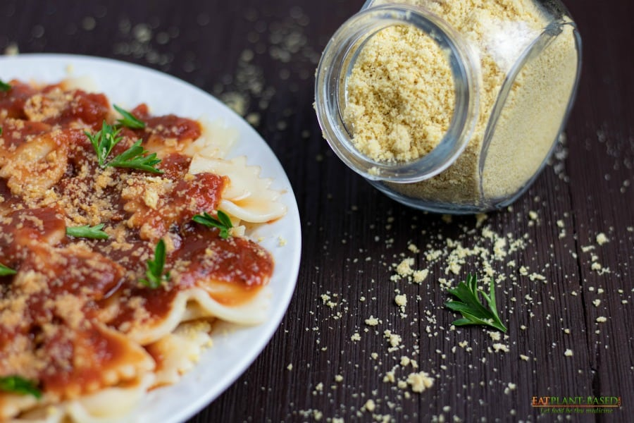 vegan parmesan cheese in a glass jar on wooden table with plate of pasta