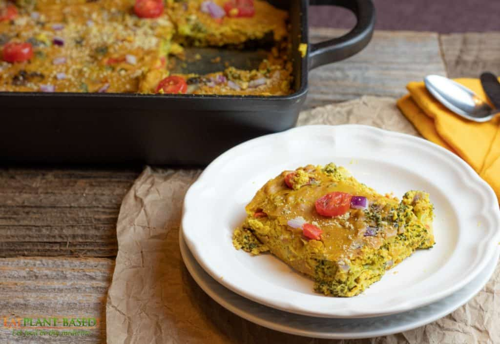 veggie quiche slice on stacked white plates on wooden table with casserole pan in background